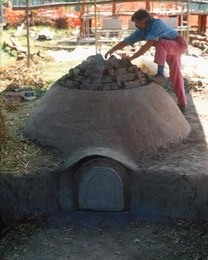 Final phase in building a pottery kiln. The structure comprises a circular combustion chamber with a protruding dome in compacted clay and vegetable fibre. The mouth takes in air, which is funnelled through a chimney at the rear to favour and control the flow.