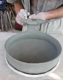 Once the shape has been achieved, handles and grips are added; these are often particularly elaborate in the case of terramare pottery.