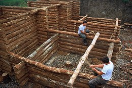 Building the entrance and the village fortifications: notice the wooden cages filled with earth.