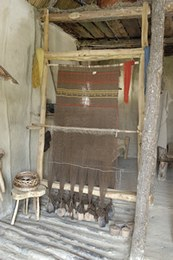 The larger of the looms has been set up for weaving linen (flax). It comprises 650 threads held by 32 weights.