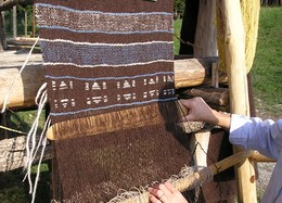 In a loom using weights, the cloth is woven from the bottom up using wooden spatulas.