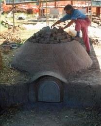 Fase finale della costruzione della fornace. La struttura è composta da una camera di combustione circolare a cupola realizzata in terra argillosa impastata con fibre vegetali, munita di un'imboccatura frontale da un camino retrostante per favorire e controllare il flusso d'aria