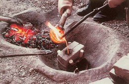 Al raggiungimento della fusione del metallo, segue la colatura del bronzo all'interno della forma di fusione, preventivamente disposta accanto alla fossa per favorire il preriscaldamento della pietra