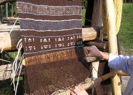 Nel telaio a pesi la tessitura avviene inserendo la trama dal basso verso l'alto con l'aiuto di spade di legno