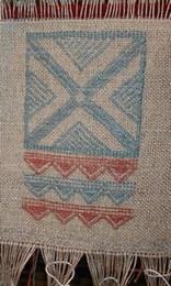 Particolare di un tessuto in lino con decorazione a broccato   Con il guado sono state ricavati filati di diverse tonalità di azzurro. I tessuti realizzati sui due telai di Montale sono decorati con motivi tratti dall'iconografia della ceramica della terramara. La tecnica tessile utilizzata per la decorazione è il broccato